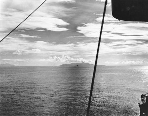 "Figure 4: A U.S. destroyer steams up what later became known as ""Iron Bottom Sound"", the body of water between Guadalcanal and Tulagi, during landings on both islands, 7 August 1942. Savo Island is in the center distance and Cape Esperance, on Guadalcanal, is at the left. Photographed from USS San Juan (CL-54) from a location approximately due east from the northern tip of Savo Island. (National Archives, 80-G-13539)"