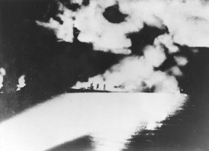 Figure 5: A victim of insufficient pre-war preparation, USS Quincy (CA-39), photographed from a Japanese cruiser during the Battle of Savo Island, off Guadalcanal, 9 August 1942. Quincy, seen here burning and illuminated by Japanese searchlights, was sunk in this action. (Naval History and Heritage Command, NH 50346)