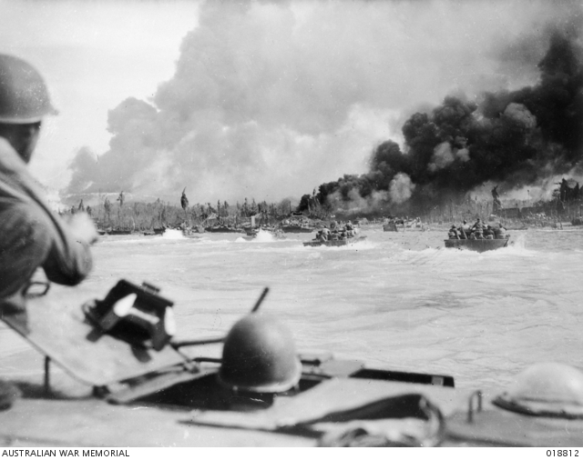 Last dash to shore, aboard American manned Alligators, during the landing of Australian troops at Balikpapan, Borneo. Smoke from the ruins of enemy positions and burning oil wells is visible in the background. Shore installations were subjected to an intensive naval bombardment before the landing operation. (Australian War Memorial ID #018812)