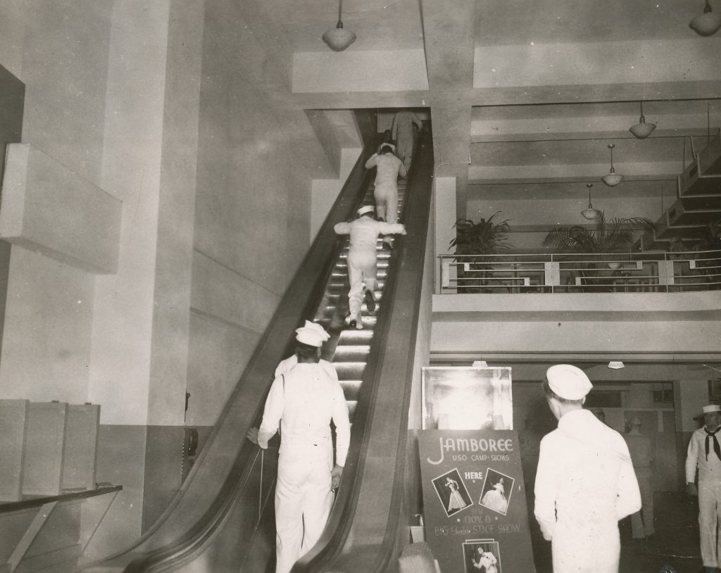 Sailors on the escalator in the lobby of the USO Victory Club.